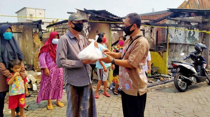 Perwakilan MCCC Krembangan, Sutikno (baju coklat), secara simbolis serahkan bantuan kepada Sungkono (Ketua RT 9) korban kebakaran di Tambak Asri Surabaya