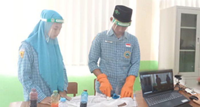 Siswa SMP Wachid Hasjim 5 Menur Surabaya, Indri dan Didik, mendemokan proses pembuatan batik ikat dalam ujian praktek kelulusan yang tayangan secara live streaming ke semua siswa kelas 9 dan guru.