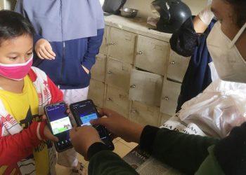 Siswa menunjukan barcode (kupon) daging kurban kepada panitia SD Muhammadiyah 12 Surabaya.